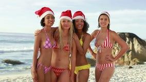 Fyra flickor som tillsammans poserar i bikinier lager videofilmer