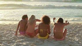Fyra flickor som tillsammans sitter på stranden stock video