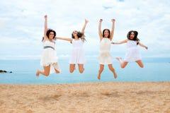 Fyra flickvänner som hoppar på stranden royaltyfri foto