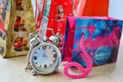 Fyra gåvapåsar och en klocka Arkivbilder
