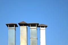 Fyra galvaniserat lampglasrör eller lufthålrör i rad Arkivbilder
