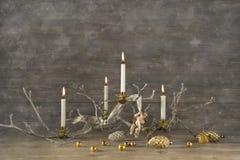 Fyra gamla brinnande adventstearinljus på trälantlig julbackg Arkivbild