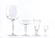 Fyra genomskinliga eleganta crystal exponeringsglas för coctailar fodrade bredvid de på en vit bakgrund Arkivfoton