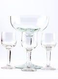 Fyra genomskinliga eleganta crystal exponeringsglas för coctailar på en vit bakgrund Royaltyfri Fotografi