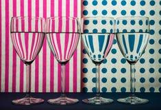 Fyra genomskinliga exponeringsglas för vin som står i linje och vit bakgrund med rosa band och blåa fläckar royaltyfria foton