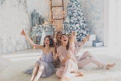 Fyra glade nätta vänner som firar partiet för det nya året eller födelsedag, har gyckel, drinkalkohol som dansar Emotionella fram Royaltyfri Fotografi