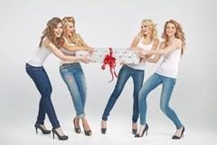 Fyra gladlynta flickor som slåss för gåva Royaltyfria Bilder