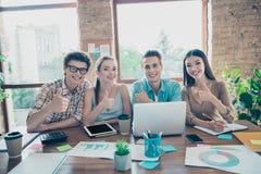 Fyra gladlynta glade tillfredsställda personer, grabbar och flickor, vänner sitter royaltyfri bild