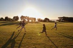 Fyra grundskolabarn som kör i ett öppet fält arkivfoton