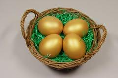 Fyra guld- ägg i korg Arkivbild
