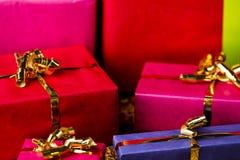 Fyra guld- pilbågar runt om slågna in gåvor Royaltyfria Foton