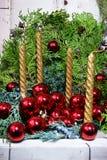 Fyra guld- stearinljus och röda julbollar Arkivbilder