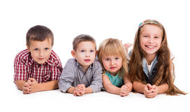 Fyra gulliga barn som ligger på golvet Royaltyfria Bilder