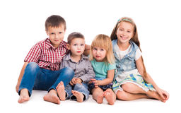 Fyra gulliga barn som sitter på golvet Arkivfoto