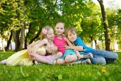 Fyra gulliga lilla barn som har gyckel tillsammans på gräset på en solig sommardag Roliga ungar som tillsammans utomhus hänger Arkivbilder