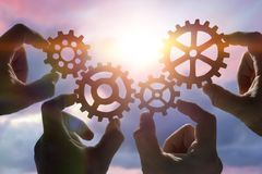 Fyra händer mot efterkrav ett pussel av kugghjul, mot bakgrunden av himlen på solnedgången royaltyfria bilder