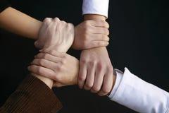 fyra händer som rymmer stram toget Royaltyfri Bild