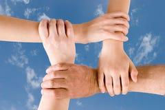 fyra händer som tillsammans sammanfogas Arkivbild
