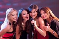Fyra härliga flickor som sjunger karaoke Royaltyfri Foto