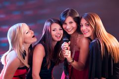 Fyra härliga flickor som sjunger karaoke Arkivfoto