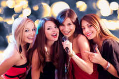 Fyra härliga flickor som sjunger karaoke Royaltyfria Bilder