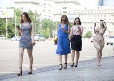 Fyra härliga modeflickor som går på gatan Royaltyfria Foton