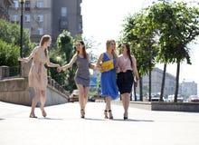 Fyra härliga modeflickor som går på gatan Royaltyfri Bild