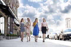 Fyra härliga modeflickor som går på gatan Arkivbilder
