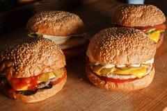 Fyra hamburgare på brädet royaltyfria foton