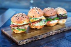 Fyra hamburgare på träbräde i restaurang arkivfoto