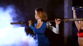 Fyra idrotts- sexiga kvinnor som gör kondition, övar med weightings, på natten, i ljus rök, dimma, i ljus av a lager videofilmer