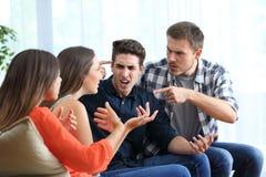 Fyra ilskna vänner som hemma argumenterar royaltyfri fotografi