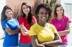 Fyra internationella flickor med korsade armar som är utomhus- i staden Arkivbilder