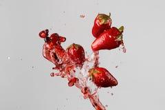 Fyra jordgubbar och röd fruktsaftfärgstänk Royaltyfria Bilder