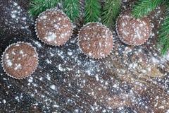 Fyra julkakor på insnöad träbakgrund för vinter, gran Royaltyfri Foto