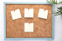 Fyra klisterm?rkear eller mellanrum p? en corkboard, begrepp av meddelanden, kopieringsutrymme, begrepp av planl?ggningen eller p arkivfoto