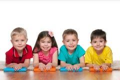Fyra klyftiga barn med böcker Royaltyfria Bilder