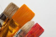 Fyra konstnärliga borstar på vit bakgrund arkivfoton