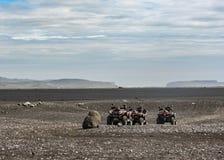 Fyra kvadratcyklar i ställe för Solheimasandur nivåhaveri: svart sandökenlandskap i södra Island, Europa royaltyfri foto