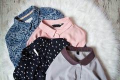 Fyra kvinnliga skjortor på vit päls, sortiment för begreppsframsida för skönhet blå ljus kvinna för makeup för mode Royaltyfri Foto