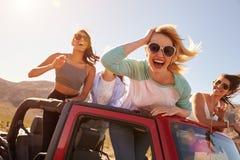 Fyra kvinnliga vänner på anseende för vägtur i konvertibel bil Royaltyfri Bild