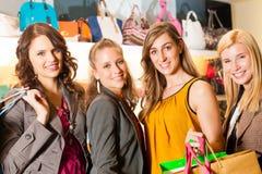 Fyra kvinnligvänner som shoppar påsar i en galleria Arkivbilder