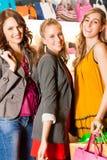 Fyra kvinnligvänner som shoppar påsar i en galleria Arkivbild