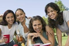 Fyra kvinnor på den utomhus- picknicken. Royaltyfri Bild