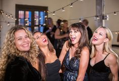 Fyra kvinnor som högt skrattar på ett parti Royaltyfri Foto