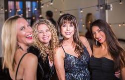 Fyra kvinnor som ler på ett parti Arkivbild