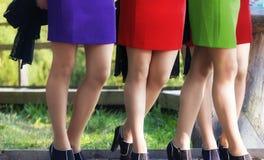 Fyra kvinnors ben med färgrika kjolar Arkivfoto