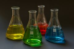 Fyra laboratoriumflaskor med flytande royaltyfria foton