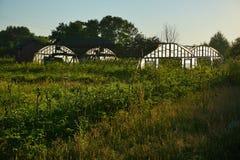 Fyra lilla gröna hus i det åkerbruka fältet Arkivfoto
