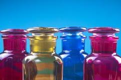 Fyra lite färgade flaskor och deras glass stordia Fotografering för Bildbyråer